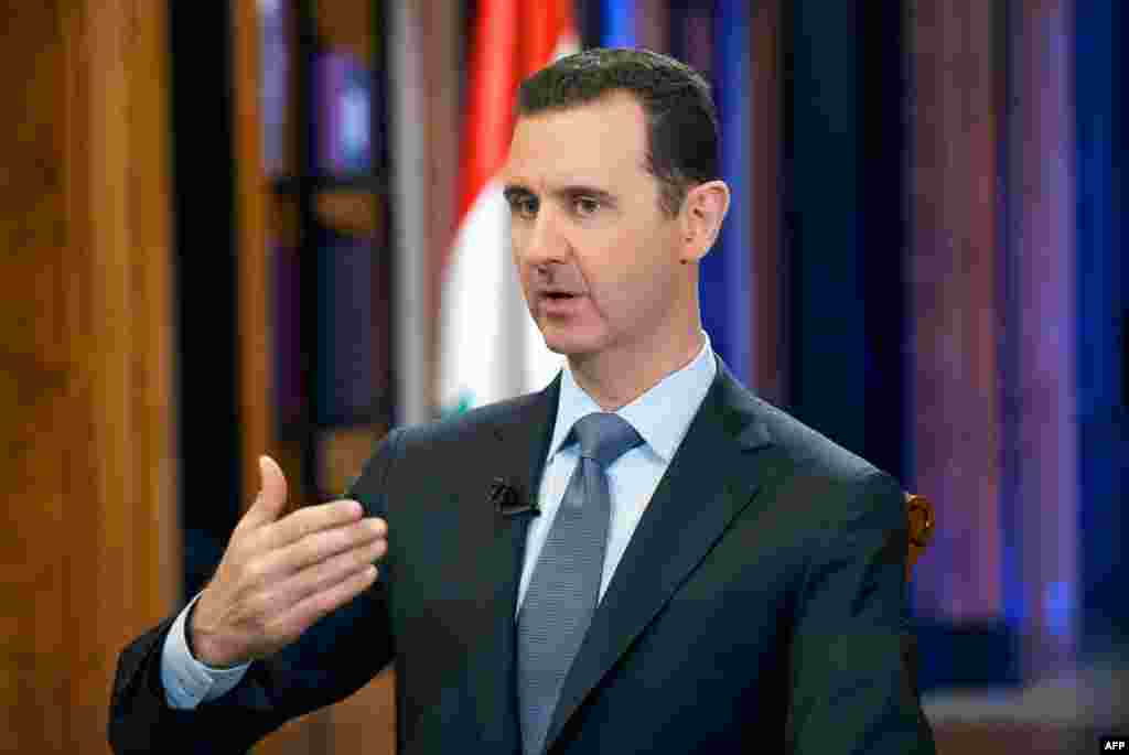 18 сентября Совбез ООН не смог достичь компромисса для принятия резолюции по Сирии. Одобрение этого документа является одним из ключевых этапов внедрения плана США и России по уничтожению химического арсенала Дамаска в течение года. Президент Сирии Башар Асад тем временем заявил, что на уничтожение химоружия понадобится год и около миллиарда долларов США. В интервью Fox News 18 сентября Асад сказал, что «убедительные и очевидные доказательства» применения зарина, о которых говорится в докладе, представленном экспертами ООН, на самом деле «нереалистичны». На фото: президент Сирии Башар Асад. Дамаск, 19 сентября 2013 года.