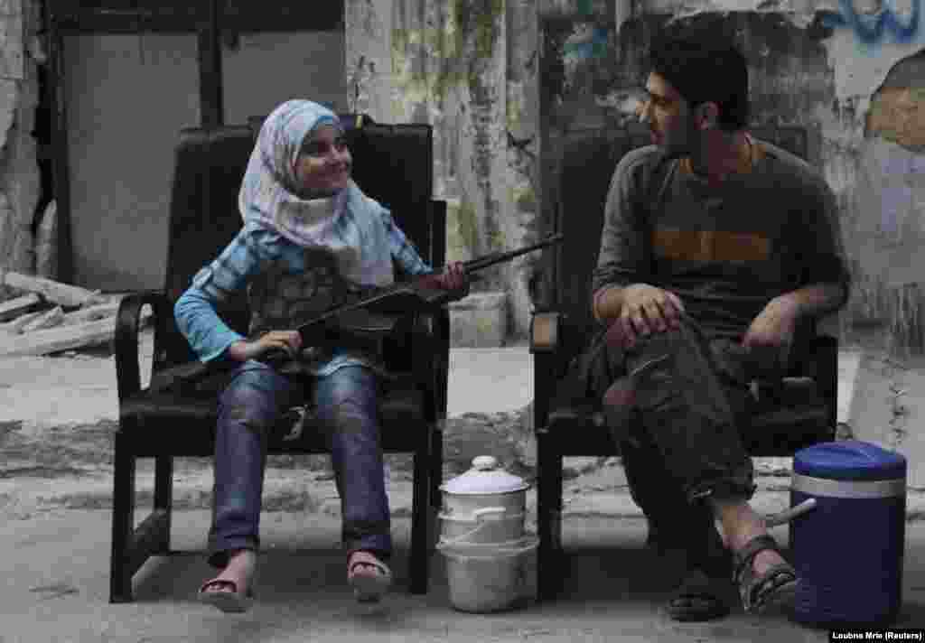 A girl holds a gun across her lap as she sits with a Free Syrian Army fighter on a street in Aleppo. (Reuters/Loubna Mrie)