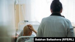 Сотрудница алматинского хосписа входит в палату пациентки.