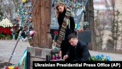 Ukrainian President Volodymyr Zelenskiy and his wife, Olena, pay their respects at the memorial dedicated to people who died in clashes with security forces in 2014 at Independence Square in Kyiv on February 20.
