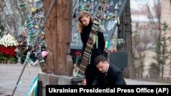 Presidenti ukrainas, Volodymyr Zelenskiy, dhe gruaja e tij, Olena, bëjnë nderimet e tyre në memorialin kushtuar njerëzve që vdiqën në përleshjet me forcat e sigurisë në Kiev, në vitin 2014.