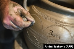"A potter twirls some ornamentation and the word ""Zlakusa"" into a raw pot before setting it to dry."