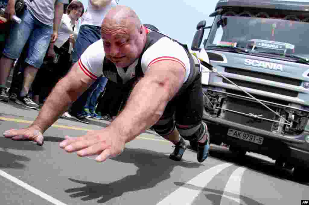 An athlete pulls a 15-ton truck during a truck-pull event marking Belarus's upcoming Independence Day in the capital, Minsk, on July 3. (AFP/Sergei Gapon)