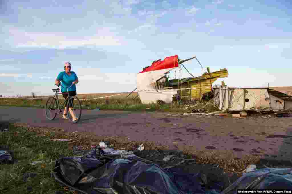 A woman passes by the wreckage of MH17 on July 20, 2014.