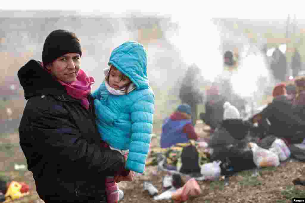 A migrant from Afghanistan holds his daughter as they wait on a roadside near Turkey's Ipsala border crossing with Greece. (Reuters/Murad Sezer)