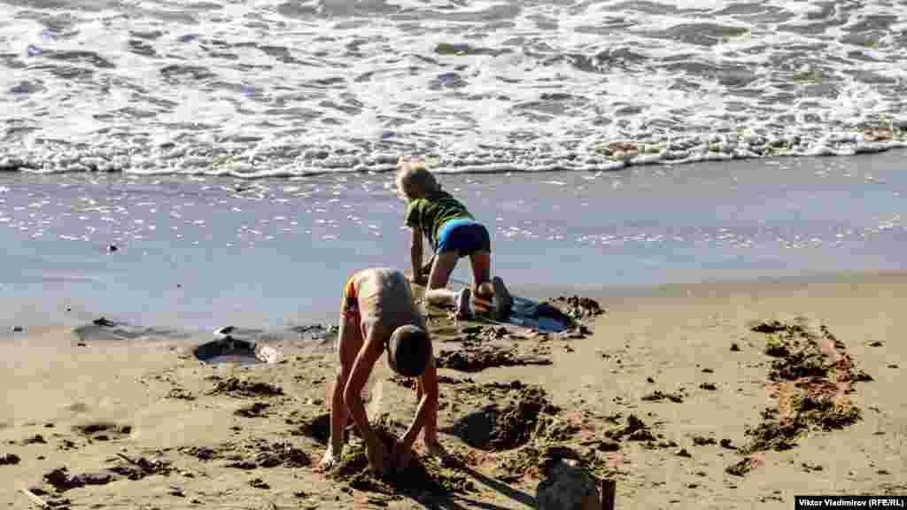 Дети лепят песочные фигуры на берегу