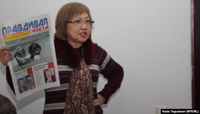 """Розлана Таукина, редактор """"Правдивой газеты"""", показывает в суде один из номеров издания. Алматы, 10 февраля 2014 года."""