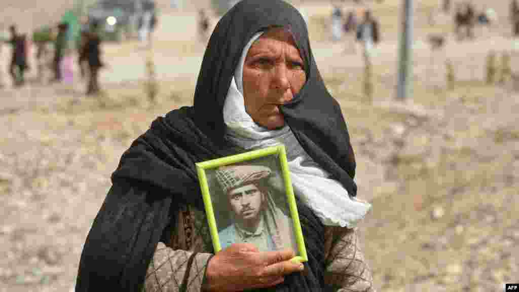 An Afghan woman holds a photograph of her dead son on the outskirts of the city of Herat after a memorial service. (AFP/Aref Karimi)