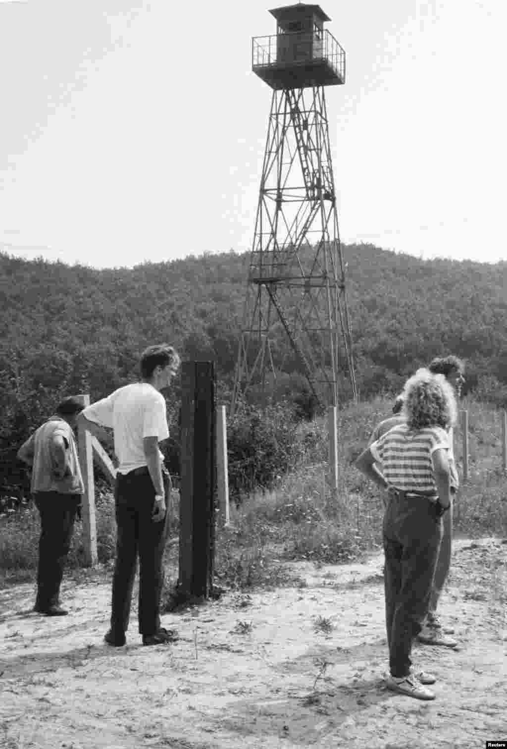 East German refugees observe the Austrian border within sight of a Hungarian watchtower on August 17.