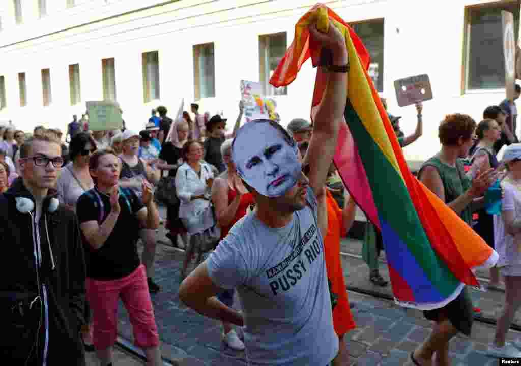 Человек в картонной маске с изображением президента России Владимира Путина несет радужный флаг ЛГБТ-сообщества