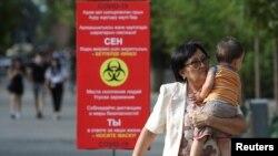 Люди проходят мимо плаката с информацией о мерах профилактики коронавирусной инфекции. Алматы, 12 июля 2020 года. REUTERS/Pavel Mikheyev.