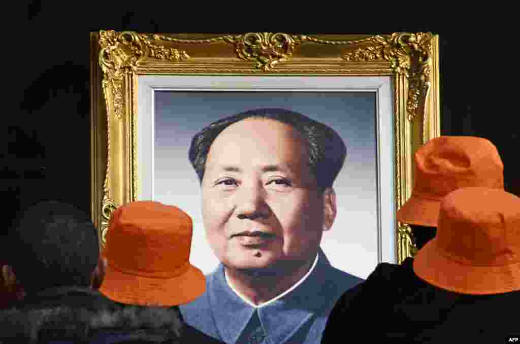 People look at a portrait of former Chinese leader Mao Zedong at a studio in Beijing.
