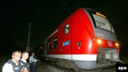 Police stand by a regional train in Germany where an Afghan man wielding an ax attacked passengers.