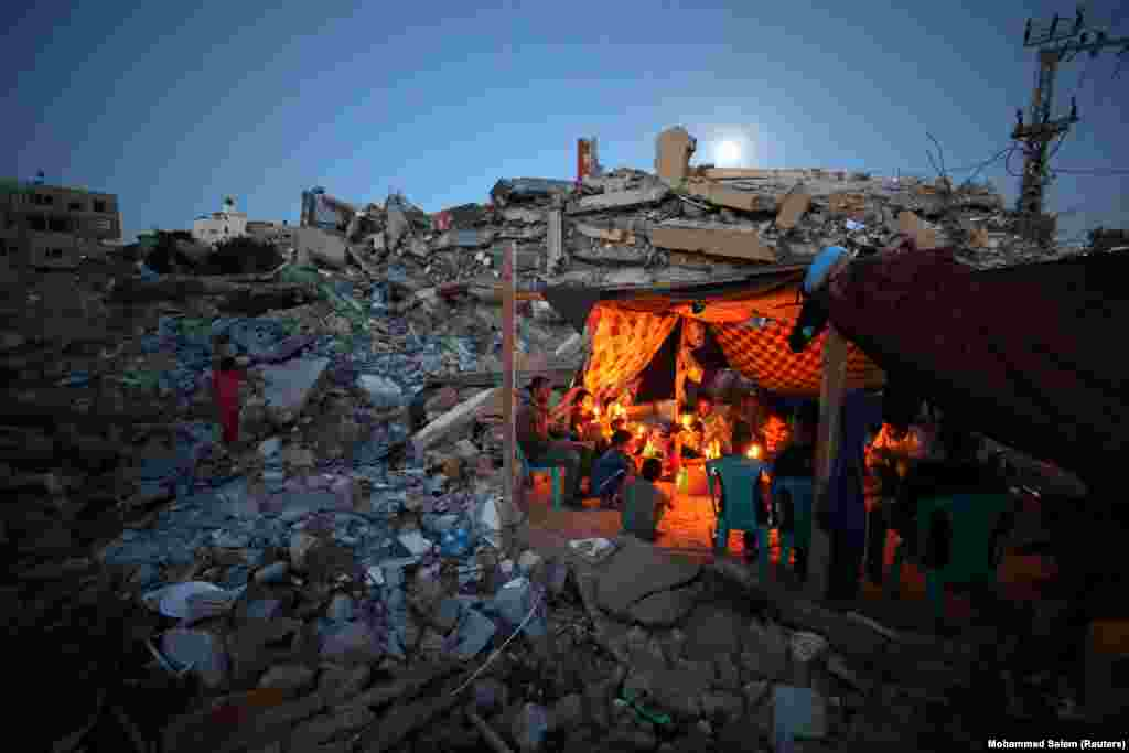 Palestinians from Zawaraa family hold candles as they sit in a makeshift tent amid the rubble of their houses which were destroyed by Israeli air strikes during the Israeli-Palestinian fighting in Gaza, May 25, 2021.