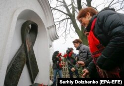 U.S. Ambassador to Ukraine Marie Yovanovitch lays flowers at a memorial to people who have died of AIDS in Kyiv in November.