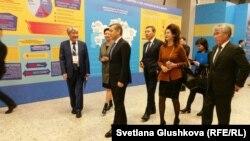 Президент «Гражданского альянса Казахстана» Нурлан Еримбетов (слева) показывает выставку достижений НПО Казахстана министрам и депутатам парламента. Астана, 25 ноября 2016 года.