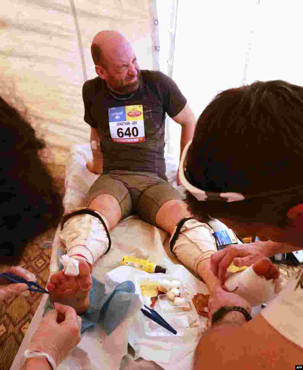A competitor receives treatement on his feet during the 28th edition of the grueling 224-kilometer Marathon des Sables in Morocco. Competitors must carry all of their equipment on their backs during the seven-day race. Only carefully rationed bottles of water and open-sided local tents are provided by the organizers. (AFP/Pierre Verdy)