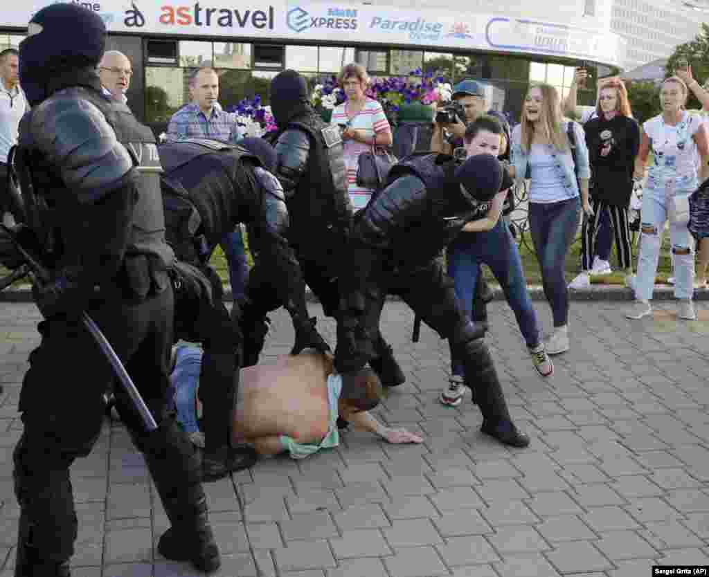 Security forces struggle with protesters in Minsk.