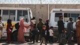 Люди выстраиваются в очередь на посадку в автобусы в международном аэропорту в Кабуле во время эвакуации, 22 августа 2021 года
