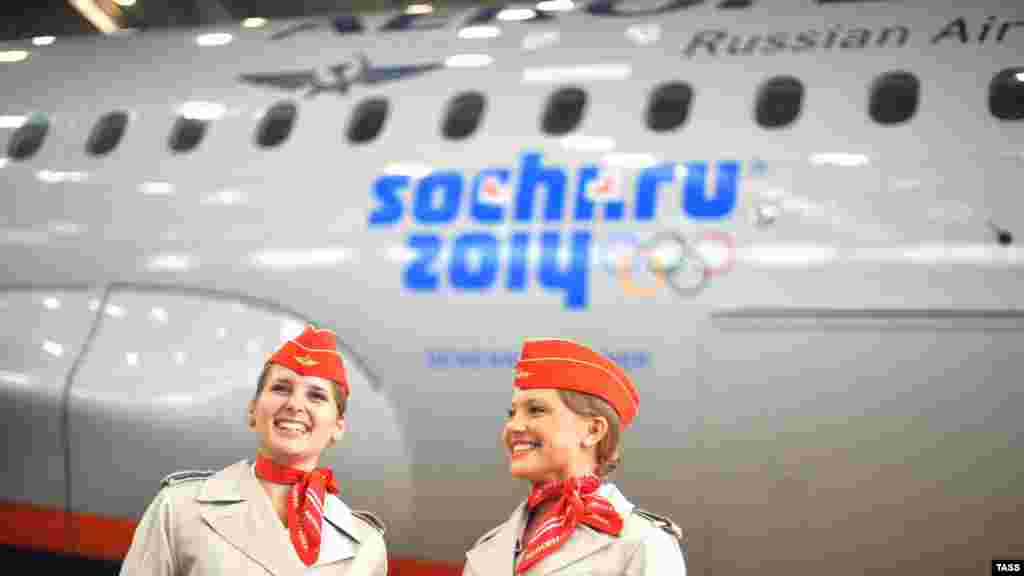 Aeroflot stewardesses stand in front of a passenger plane with the Sochi 2014 Winter Olympic Games logo in Moscow in May 2012.
