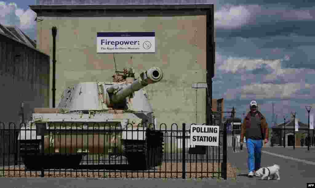 A man walks his dog past a tank with a Howitzer gun outside the Greenwich Heritage Centre, set up as a polling station for Britain's general election in London on May 7. (AFP/Daniel Sorabji)