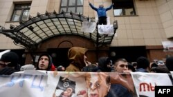 Russian protesters hold up a poster showing Turkish President Recep Tayyip Erdogan as a puppet of Islamic State militants during a rally in front of the Turkish Embassy in Moscow on November 25.