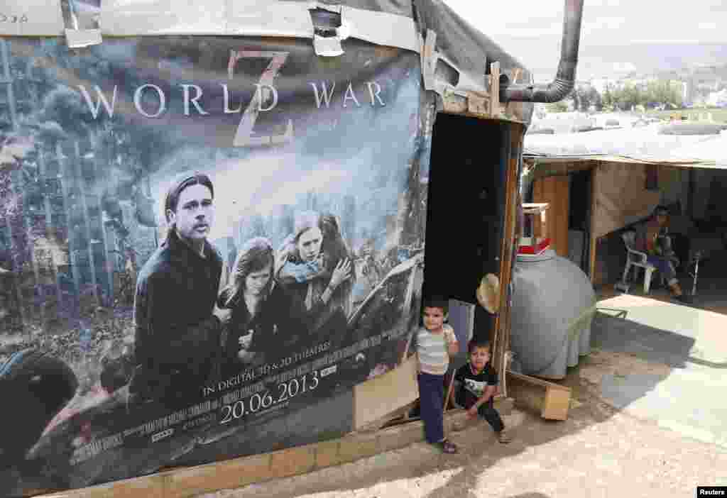Syrian refugees rest beside a film poster being used as part of a tent in an informal settlement in Zahle in the Bekaa Valley, Lebanon. (Reuters/ Mohamed Azakir)