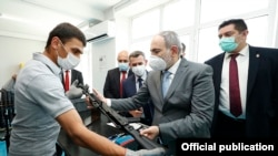 Armenia -- A worker shows Prime Minister Nikol Pashinian a Kalashnikov AK-103 rifle assembled at the Neitron company plant in Abovian, July 7, 2020.