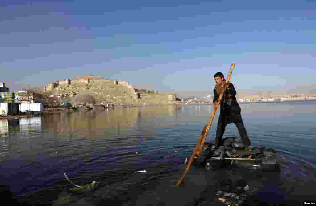 An Afghan boy rows a homemade raft on a lake in Kabul. (Reuters/Mohammad Ismail)