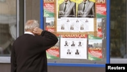 Ілюстрацыйнае фота, мянчук разглядае плякаты перад парлямэнцкімі выбарамі 2012 году
