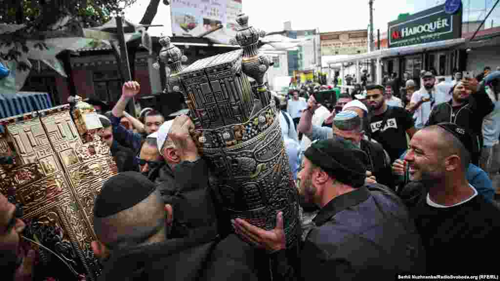 Pilgrims carry an elaborate Torah case through the streets of Uman.