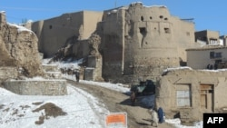 "People walk past a section of the old city in Ghazni, which means ""jewel."""