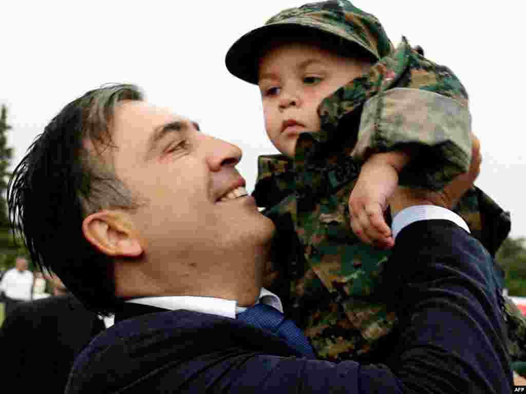 Dete u uniformi - Predsednik Gruzije Mihael Sakašvili drži dete obučeno u vojnu uniformu Gruzije prilikom obeležavanja godišnjice konflikta sa Rusijom oko Južne Osetije.