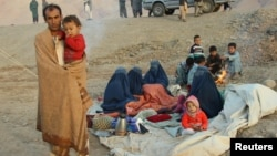 An Afghan family waits for help from the government and aid organizations in Takhar after fleeing their homes in neighboring Kunduz province on October 12.