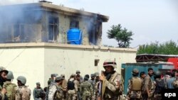 Afghanistan -- Afghan security officials take up positions at the scene of an attack by Taliban militants targeting the justice office in Jalalabad city, provincial capital of Nangarhar Province, May 12, 2014