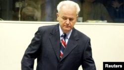 Former Yugoslav President Slobodan Milosevic enters a courtroom in The Hague in August 2004.