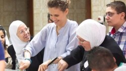 Smiling for the camera: the Syrian first lady preparing food for needy families during Ramadan.