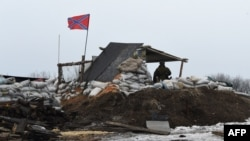 A pro-Russian soldier stands guard at a checkpoint in Enakieve, 25 kilometers from the eastern town of Debaltsevo, on January 29.