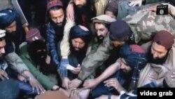 «Ислам мемлекеті» тобы басшысы Әбу Бәкір әл-Бағдадиге адал болуға серт беріп жатқан ӨИҚ содырлары. (Видеодан скриншот)