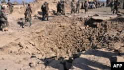 FILE: Afghan soldiers stand near a crater after a car bomb exploded which targeted an Afghan National Army (ANA) base in Khost province in March.