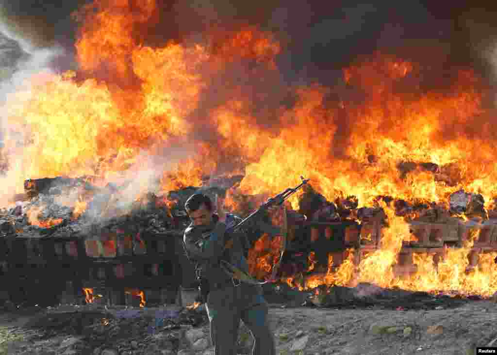 An Afghan officer reacts in front of a burning pile of seized narcotics and alcoholic drinks on the outskirts of Kabul. (Reuters/Omar Sobhani)