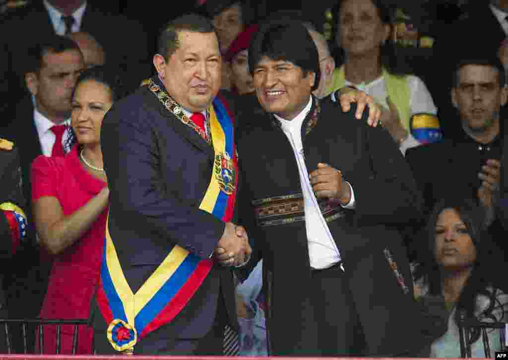 Chavez greets his Bolivian counterpart, Evo Morales (right), during a military parade to commemorate the 20th anniversary of his failed coup attempt on February 4, 2012.