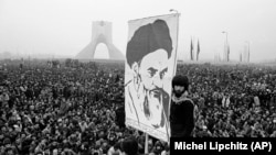 In this Dec. 10, 1978 file photo, demonstrators hold up a poster of exiled Muslim leader Ayatollah Ruhollah Khomeini during an anti-shah demonstration in Tehran, Iran. Khomeini would soon return to establish a religious authoritarian regime.