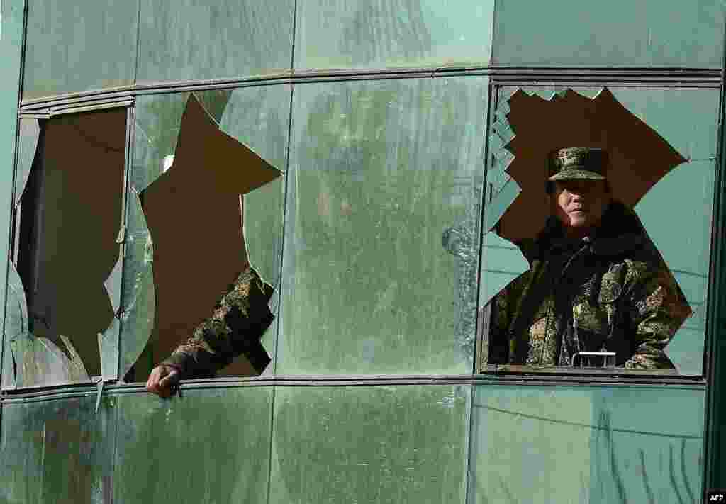 Afghan security forces look through a broken window after a clash between Afghan forces and Taliban fighters in Kabul. (AFP/Shah Marai)