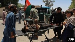Afghan men carry a victim of a powerful car bomb in Lashkar Gah on June 22.