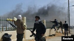 Rebels run after an air strike by pro-Qaddafi forces in the eastern city of Ras Lanouf on March 8.