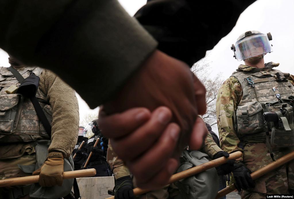 Kéz a kézben állnak a tüntetők a Nemzeti Gárdával szemben.