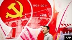 Қытай коммунистік партиясының 90 жылдығы құрметіне жасалған баннер алдында тұрған адам. Шанхай, 1 шілде 2011 жыл.