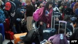 Italian tourists rest in the departure hall of Prague's Ruzyne Airport.