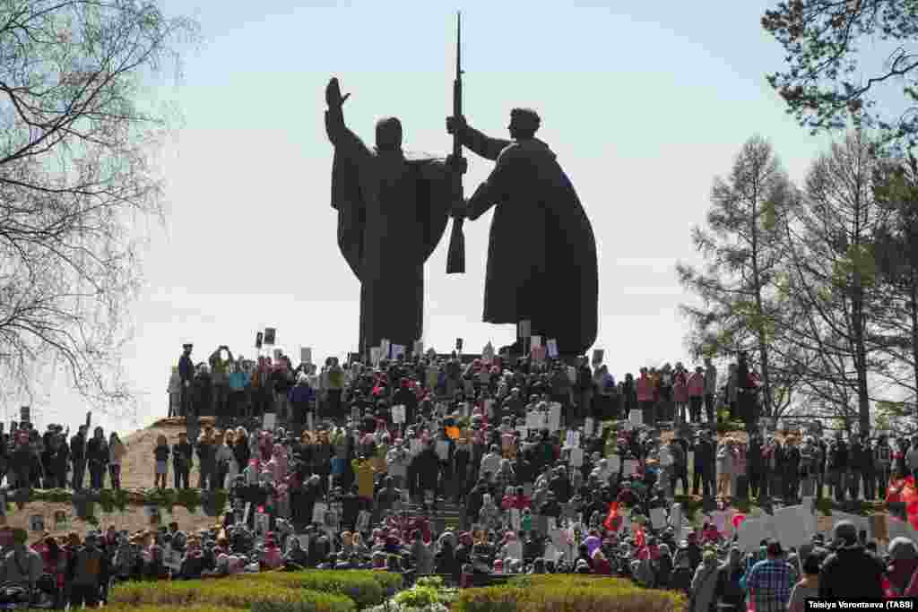 People with portraits of their relatives who fought in World War II gather at the monument, called Motherland Hands A Weapon To Her Son, in the city of Tomsk on May 9, 2019, to mark the 74th anniversary of Soviet victory in the Great Patriotic War.